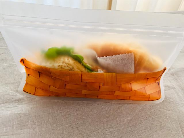 サンドイッチとロールパンを入れてジップを閉めたバッグ