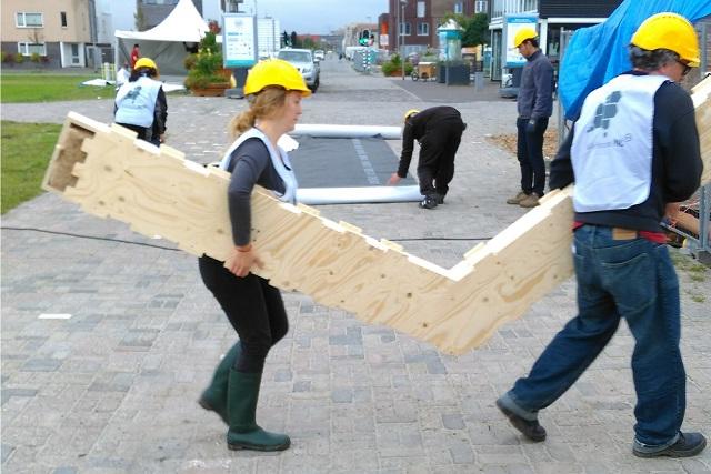 カットされた木材を運ぶボランティアたち