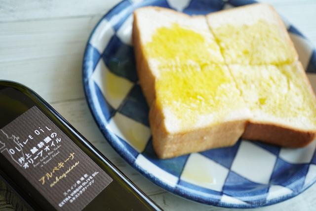 オリーブオイルの瓶とオリーブオイルをかけた食パン