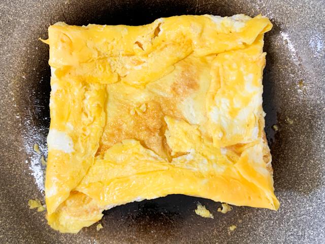 パンから飛び出ている卵をパンの形に折り畳んで行きます