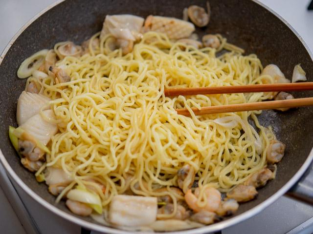 調味料と麺を入れて炒める